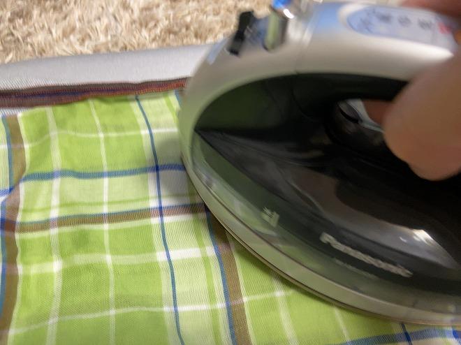 ジョグジーンズの上に補修布を敷き、その上にハンカチを敷いてアイロンをかけている画像