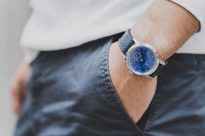 服装とうまくコーディネートできた腕時計をする男性