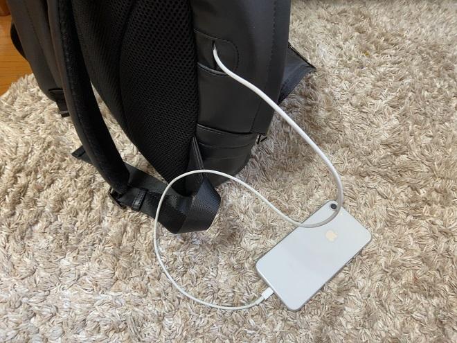 THE ONEのメイン収納部のポケットに入れたモバイルバッテリーに付けたアイフォン充電用USBケーブルを背面穴から外に出してiphone8を充電いている画像