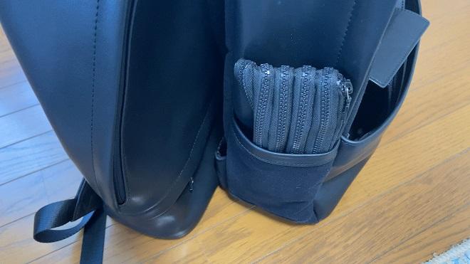 TSOGリュックTHE ONEとMUKOの側面を比較している画像。MUKOのサイドポケットにペン入れを収納している様子